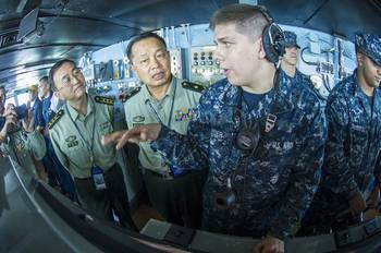 File Seaman Alex Snyder, right, explains the functions of the helm on the navigation bridge of the aircraft carrier USS George Washington to Maj. Gen. Chen Weizhan, deputy commander of the People