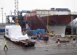 File The Rolls-Royce MT30 gas turbine enclosure, shrink wrapped for protection, arrives alongside HMS Queen Elizabeth, prior to installation at Babcock's Rosyth yard in Scotland.
