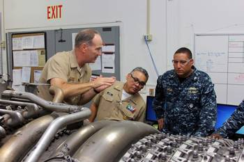 File Capt. James S. Talbert, production officer at Norfolk Ship Support Activity, explains the change-out process of an LM2500 gas turbine engine to Rear Adm. Gregorio Martinez Nunez, Director of Mexican Navy General Staff, as Lt. Cmdr. Vargas interprets. (U.S. Navy photo by Art B. Ladle)