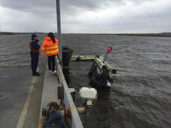 File A Coast Guardsman from the Marine Safety Unit Port Arthur stands at the edge of Black Bayou Bridge observing a damaged fender after it was hit by a boat that lost steering March 7, 2016. (U.S. Coast Guard photo by Jennifer Andrew)