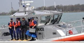 File Members of Coast Guard Station Belle Isle in Detroit, and a member of the Royal Canadian Mounted Police pose for a photo on a 45-foot patrol boat after conducting a joint patrol in Lake Erie, May 8, 2014. (USCG Guard photo courtesy of Coast Guard Sector Detroit)