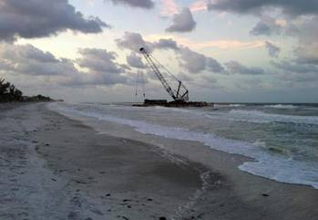 File A 140-foot barge is shown beached on Long Boat Key, Fla., Wednesday, April 9, 2014. Due to weather conditions, the barge spuds were unable to hold the barge in position and it began drifting until it ran aground on the beach at Long Boat Key. (U.S. Coast Guard photo)