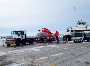 File A Dolphin helicopter from Coast Guard Air Station Traverse City, Mich., arrives at Northport Pier in Door County, Wis., on a flatbed trailer March 3, 2014 following a brief ferry transit from Washington Island. (USCG photo)