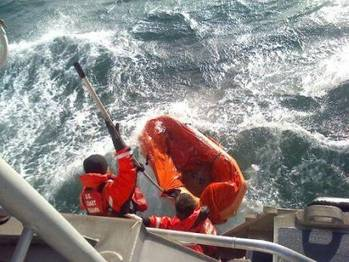 File Coast Guard crewmembers use a boat hook to pull in a empty life raft after rescuing a man who abandoned his sinking sailing vessel ( U.S. Coast Guard photo by Seaman Alyssa Petty)