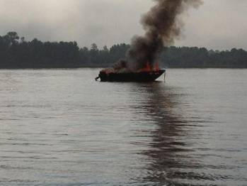 File A 17-foot pleasure craft is fully engulfed in flames near Sugar Island on the St. Marys River, Aug. 29, 2013. U.S. Coast Guard photo by Petty Officer 1st Class Joseph Kerr, executive petty officer of Station Sault Ste. Marie.