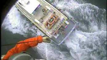 File A Coast Guard rescue swimmer is lowered to the Osprey II and a man suffering from chest pains is hoisted back up Saturday near Port Mansfield, Texas. U.S. Coast Guard video by Air Station Corpus Christi.