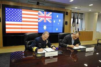 File Rear Adm. Christopher Tomney signs a MOU with Michael Pezzullo, CEO of the Australian Customs and Border Protection Service, at Coast Guard Headquarters in Washington, D.C. (U.S. Coast Guard photo by Petty Officer 1st Class Timothy Tamargo)