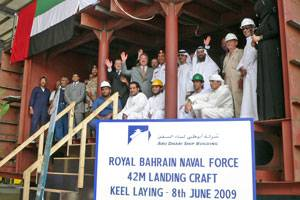 File Staff Colonel Hasan Ahmed Mohammed, Head of the Planning Department, Royal Bahrain Naval Force and ADSB CEO Bill Saltzer with ADSB management and employees inside the first hull block constructed for the landing craft.