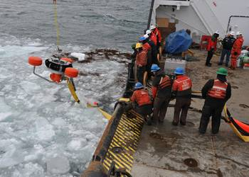 File USCG crewmembers used an oil-skimming device to recover peat moss, acting as a substitute for spilled oil, near Mackinac Island.
