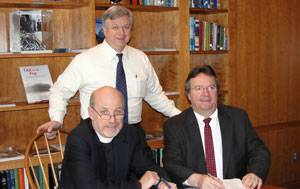 File Eric Larsson (standing), Director of Maritime Education, and SCI's President & Executive Director, the Rev. David M. Rider (L), sign the contract for the first phase of SCI's Houston simulator upgrades with Kongsberg Maritime, represented by Area Sales Manager Henry Tremblay (R).