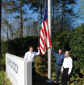 File Martin Magill, Senior Vice President; Pierre Tanguay, VP Supply Chain; and Angelyn Gill, Health Safety and Environmental Coordinator, raising the flag at Wheelabrator, LaGrange