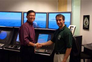 File Mark Broster of ECDIS Ltd shaking hands with LTC Terence Ho of the Republic of Singapore Navy. Photo courtesy ECDIS