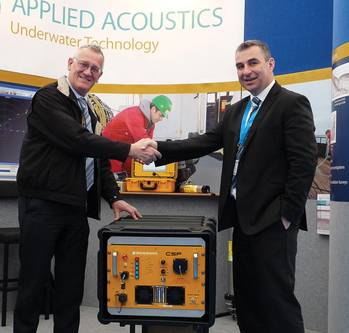 File Tom Nicols of Geomatrix left, receiving his new seismic power supply, from Applied Acoustics' Gavin Willoughby.