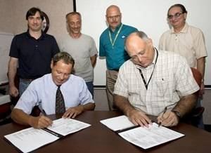 File Seated, l-r: Marty Capalbo, configuration manager for Supervisor of Shipbuilding (SUPSHIP) Gulf Coast, (left) and John Broderick, Ingalls