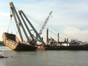File Inland Salvage Raises Scrap Metal Barge on the Mississippi River.