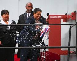 File Myrlie Evers-Wilson, the widow of slain civil rights leader Medgar Evers and ship sponsor of Military Sealift Command dry cargo/ammunition ship USNS Medgar Evers, breaks the traditional bottle of champagne against the ship