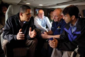File President Obama talks with Coast Guard Admiral Thad Allen, who was also the National Incident Commander for the Deepwater Horizon oil spill (center), and Louisiana Gov. Bobby Jindal aboard Marine One as they fly along the coastline from Venice, La., to New Orleans on May 2, 2010. White House Photo by Pete Souza