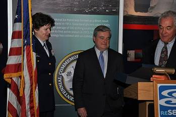 File Dr. Coan, President and Chief Executive Officer of the Sea Research Foundation, presents a plaque commemorating the centennial of the International Ice Patrol to CDR Lisa Mack, Commander of the International Ice Patrol, at the official opening of the Ice Patrol gallery at the Mystic Aquarium.