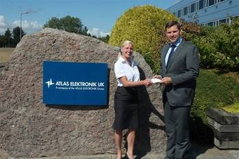File Dr. Antoni Mazur, Managing Director handing over the check for the donation from Atlas Elektronik UK to Sam West, Marketing Manager