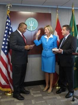 File U.S. Secretary of Transportation Anthony Foxx swearing in Betty Sutton as Administrator of the Saint Lawrence Seaway Development Corporation. Her husband Doug Corwon holds their family Bible.