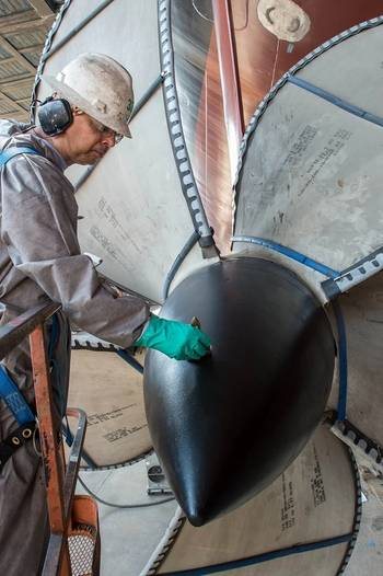 File Lindell Toombs, a Newport News shipbuilder with 41 years of experience, applies a protective coating to one of the four propellers on the aircraft carrier Gerald R. Ford (CVN 78). Photo by Chris Oxley