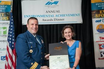 File Rear Admiral Joseph Servidio presents Susan Hayman of Foss the award for environmental achievement.