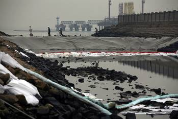 File Workers clean up oil on a river of the Jiaozhou Bay after an oil pipeline exploded at the China Petroleum & Chemical Corp. plant in the city of Qingdao, east China
