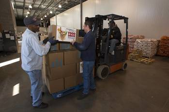 File Newport News Shipbuilding employees Rudolph Johnson (left) and Wesley Dunlow (right) load boxes of donated food on to pallets at the Virginia Peninsula Foodbank. Foodbank employee Reginald Williams operates the forklift. Photo by John Whalen