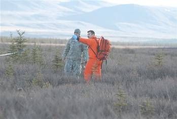 File A Canadian search-and-rescue technician points out the causality collection point to a soldier role-playing a wounded crash victim at Donnelly Training Area, Alaska, Oct. 30, 2013. The soldier is part of a Joint Task Force Alaska, Alaska National Guard, U.S. Army Alaska, Canadian Joint Operations Command arctic search-and-rescue exercise at Fort Greeley and Joint Base Elmendorf-Richardson, Alaska. U.S. Army photo