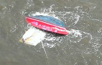 File A personal craft is capsized after a collision with a tug and barge Sunday. U.S. Coast Guard photo.