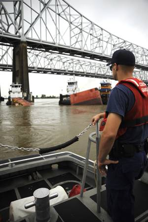 A Coast Guard crewmember aboard a 41-ft. smallboat from Coast Guard Station New Orleans overlooks the sunken barge in the Mississippi River in downtown New Orleans after the motor vessel Tintomara and a tub and barge collided early Wed. July 23, 2008 spilling approximately 419,000 gals. of number six fuel oil.  (U. S. Coast Guard photo/Petty Officer 2nd Class Thomas M. Blue)