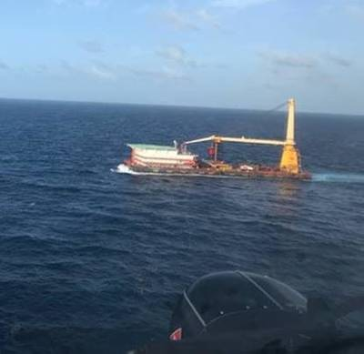 A Coast Guard helicopter crew rendezvous with the 400-foot DB Superior Performance barge June 28 2021, approximately 140 nautical miles south of Ponce, Puerto Rico during the medevac of a barge crewmember who was experiencing possible cardiac distress. (Photo: U.S. Coast Guard)