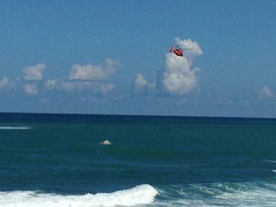 A Coast Guard rescue helicopter crew with Coast Guard Air Station Borinquen, Puerto Rico, flies over a capsized Coast Guard Station San Juan Puerto Rico smallboat off the coast of Puerto Rico Nov. 8, 2013. The smallboat search-and-rescue crew was responding with other local agencies to a report of two people in the water two nautical miles northeast of San Juan Harbor when the vessel capsized. U.S. Coast Guard photo.