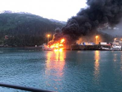 A fire burns at Delong Dock after an explosion on fixed barge in Whittier, Alaska, July 8, 2019. In addition to Coast Guard crews, response efforts included members of the Whittier Fire Department, Whittier Police Department, Anton Anderson Memorial Tunnel Fire Department and Girdwood Fire Department. Photo courtesy of Coast Guard Sector Anchorage.
