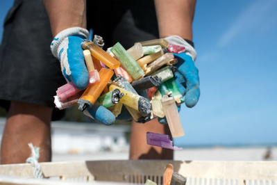 A marine debris team member gathers a handful of disposable cigarette lighters picked up at a beach cleanup site. (NOAA)