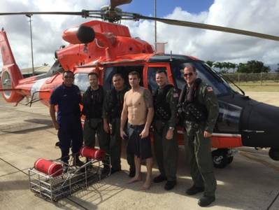 A MH-65 Dolphin helicopter crew from Coast Guard Air Station Barbers Point poses with a person they rescued Dec. 19, 2014, while on a routine patrol off Kauai. They were contacted by a tour helicopter on VHF radio channel 16 about an SOS marking written on the beach in the sand. (U.S. Coast Guard photo)