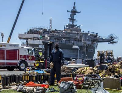 A sailor looks at firefighting gear laid out in front of the amphibious assault ship USS Bonhomme Richard (LHD 6). (U.S. Navy Photo by Natalie M. Byers)