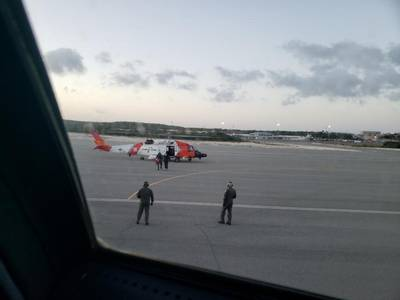 A U.S. Coast Guard helicopter crew walks an ailing mariner to an aircraft in Providenciales, Turks and Caicos, on Wednesday. The man was experiencing health complications aboard the tug Patriarch and needed higher level medical care. (U.S. Coast Guard photo)