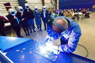 A welder authenticates the keel of LCS 21, the future USS Minneapolis-Saint Paul, by welding the initials of ship sponsor Jodi J. Greene. The Keel Laying is the formal recognition of the start of the ship's module construction process. Photo: Lockheed Martin