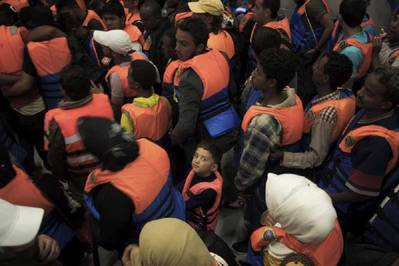 A young boy surrounded by adults after being rescued in June 2014 from a boat on the Mediterranean Sea. Photo: UNHCR/A. D'Amato