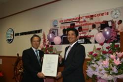 ClassNK Executive Vice President Koichi Fujiwara (L) presents NYKSM CEO Tomoyuki Koyama (R) with certificate.