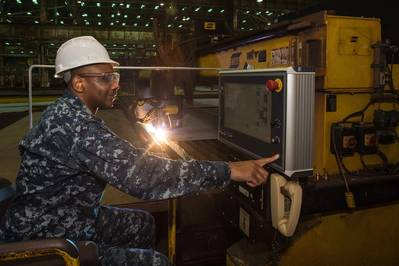 Cmdr. Dave Murray, post-delivery officer for the U.S. Navy's DDG 51 program, presses the button to start fabrication of the Ingalls-built destroyer Frank E. Petersen Jr. (DDG 121). Photo by Lance Davis/HII