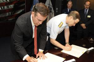 Coast Guard Rear Adm. Brian Salerno and Otto Candies, III, Vice Chairman of the Offshore Marine Services Association, sign a memorandum of understanding April 30, 2009, establishing the Offshore Support Vessel Industry Quality Partnership. This partnership promotes safety and security within the offshore industry and facilitates an open dialog between the Coast Guard and maritime stakeholders. (Coast Guard photo/Petty Officer 1st Class Mike Lutz)