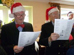 Commander Brian Boxall-Hunt OBE, Chief Executive of the Society and Capt. Braithwaite singing carols.