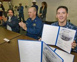 Doug Lounsberry (left) and Cmdr. Joe Tuite (center) applaud as Cmdr. Jon Haydel, commanding officer of San Diego (LPD 22), holds up the ceremonial document acknowledging the ship's custody transfer from Huntington Ingalls Industries to the U.S. Navy. Lounsberry is vice president of the LPD 17 Program at Ingalls. (Photo: HII)