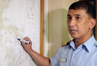 The Philippine coastguard spokesman points to the area on a map where a ferry went down on June 14, 2013 (AFP/File, Jay Directo)