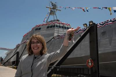 "Former U.S. Rep. Gabrielle ""Gabby"" Giffords waves to a crowd in front of the littoral combat ship, USS Gabrielle Giffords (LCS 10). (Photo courtesy Austal USA/Released)"
