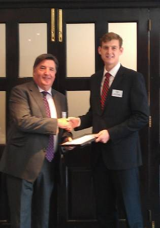 James Temple (right) receiving his certificate from Mr Archie Bethel CBE