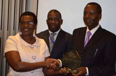 Kenya's Minister of Tranasport, Mr Amos Kimunya recieves a trophy from Ms Nancy Karigithu, Director General, Kenya Maritime Authority.