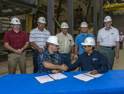 Lt. Cmdr. Stephen Blevins (seated, left) shakes hands with John Fillmore. Blevins is the Navy's DDG 1000 program manager at Supervisor of Shipbuilding Gulf Coast; Fillmore is Ingalls' DDG 1000 program manager for deckhouse and hangar. Standing (left to right) are Jonathan Graves, deputy program manager's representative, SupShip Gulf Coast; Jeff Roberts, DDG 1000 program management; Neil Adams, general ship superintendent; Dell Simmons, composite superintendent; and Steve Sloan, DDG 1000 program
